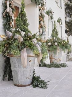 Large zinc containers with evergreens on porch decorated for Christmas