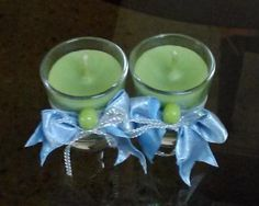Hand poured green candles in shot glasses decorated with blue ribbons and green ceramic beads