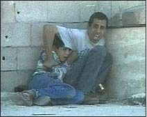 Captured from a film showing the Palestinian father, Jamil ad-Durra, trying to protect his son from israeli gunfire moments before the boy was shot dead, the father wounded and a Palestinian ambulance driver who came to rescue them, also killed.