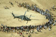 Curious Iraqis gather around a US Army Blackhawk helicopter outside a small village in northern Iraq, near the Syrian border, May 17, 2003.