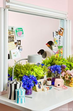 Pastel pink walls, white tabletop, large mirror with lights, grey lamp, artwork and cards on mirror, an assortment of flowers, striped canisters, and pink polaroid camera // Lena Duhma's New York dressing room
