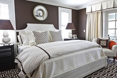 If you want your space to feel calm and balanced, it's important to introduce symmetry. People who enter a room that is arranged symmetrically will often describe it as peaceful. This is an example of great symmetry in a bedroom. The windows, the lamps, the side tables, the pillows — all harmony and sweet dreams. A room like this makes for a great night's sleep.