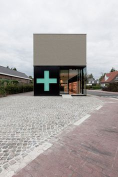 A cross-shaped window in the sliding door of this Belgian pharmacy transforms into a green sign during opening hours.