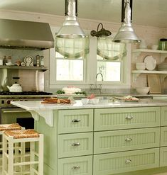 Green With Envy    The green color of the cabinets absorbs light in this open, white kitchen – white on white would have been too much.