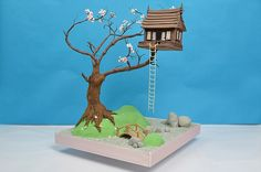 Up in the air: An idyllic tree house sits on branches made of wires covered in chocolate in a garden complete with sugar paste blossom and sugar ladder