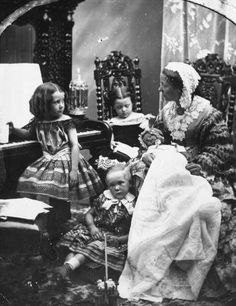 A Victorian Mother in the parlor with her children late 1800's.