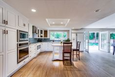 Country Modern White kitchen with light granite countertops, blue-green glass tile backsplash, and GE Frigidaire Stainless Steel appliances. Two sets of french doors lead to the backyard oasis complete with a waterfall and pond. Light Granite Countertops, White Granite Kitchen, Blue Glass Tile, Travertine Floors, Glass Tile Backsplash, Wood Laminate Flooring, Bright Kitchens, Wide Plank, Stainless Steel Appliances
