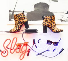 Leopard booties on a neon sign.
