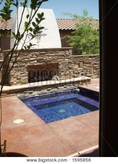 Picture or Photo of Luxurious in-ground spa and fireplace in an outdoor patio at a model home in Arizona.
