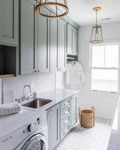 Light gray/blue cabinets in a laundry room.