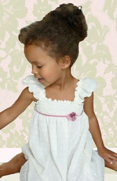 This gorgeous little dress has a shirred bust and a pink velvet ribbon sash with fabric flowers  the dress comes just below the knee and is perfect for a special occassion! ages: 2-9 years old