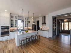 Luxurious white and gray kitchen features four backless gray French bar stools placed in front of a white shiplap island finished with a white marble countertop lit by industrial pendants.