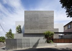 Some of the concrete walls of this house in Yokohama, Japan, were formed against wooden planks, while some have been rendered white and others have been left plain.