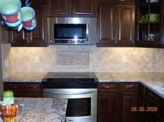 cream cabinets with back splashes brown countertop cream