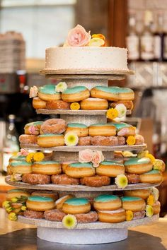 A doughnut tower with a single layer of wedding cake on top! Like the look of colored frosting and sprinkle donuts next to each other.