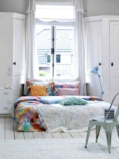 Clever shaped cupboards beside window, making it appear like a bay window. White reflecting natural light. Colourful bedding.