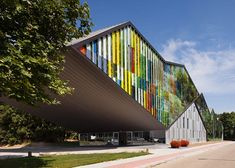 Performance centre in Belgium by Carlos Arroyo with an optical illusion on the facade featuring trees and colourful stripes.