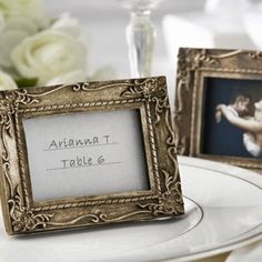 Antique place card holder/picture frame  http://www.beau-coup.com/wedding/antique-finish-place-card-holder-photo-frame.htm