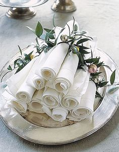 Napkin Pyramid  Instead of flat-stacking linen napkins for your guests, make a pyramid of individually rolled napkins, each ringed with greenery fastened to a mini Christmas ball with florist's wire.
