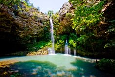 The cascade at Natural Falls State Park in northeast Oklahoma plummets 77 feet into an oasis of lush ferns and trees. A hiking trail leads down to the grotto area where deck seating is available so visitors can sit and enjoy the view. / Oklahoma, USA