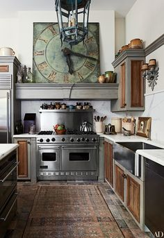 In antiques dealer Lee Stanton's Laguna Beach, California, home, the kitchen's cabinetry incorporates reclaimed English wainscoting and the clock is a French antique. | archdigest.com