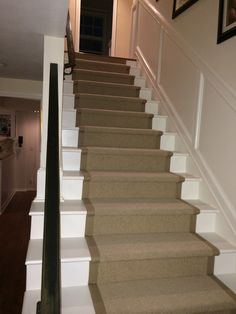 Using a piece of wool carpet that has the look of sisal, we applied a wide cotton border and installed on a staircase that was painted white.  The black railing gives the space a clean transitional look.   Purchase at Hemphill's Rugs & Carpets www.RugsAndCarpets.com
