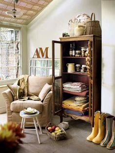 MyHomeIdeas.com - Cabinet and Chair Combo from Country Homes and Interiors: Create an instant mudroom in any room of the house by pairing an easy chair and a cabinet for storage. Rain boots don't have to be placed on a shelf to be out of the way -- just make sure items have their own designated spot. (Photo: Tim Young)