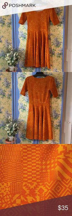 """LuLaRoe """"Nicole"""" Orange Fit and Flare Dress LuLaRoe """"Nicole"""" fit and flare style in a warm and vivid orange - on - yellow/gold geometric print. So flattering, and easy to wear. Measures 17.5"""" pit to pit; about 38"""" shoulder to hem. LuLaRoe Dresses"""