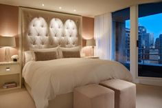 Sophisticated and relaxing master bedroom with large, upholstered ivory headboard.