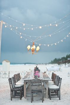 Twinkle lights and a chandelier draped over a rustic table.