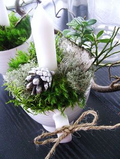Candle in a cup with acorns and moss. Simple little table decor.