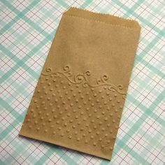 Kraft paper bags embossed with dots and scrolls. They are eco-friendly biodegradable and recyclable.