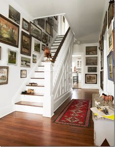 This hallway has a definite Farmhouse feel with white woodwork and walls, dark flooring and antique runner.  The eclectic mix of the gallery wall brings in much personality to this room and gives it a collected over time feel.