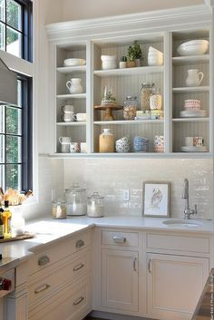 Light gray open kitchen cabinets accented with a beadboard trim are fixed above white glazed subway backsplash tiles lining a white marble countertop.