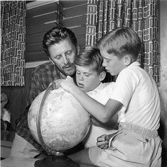 Kirk Douglas mira una bola del mundo en su casa de California, junto con dos de sus hijos, Joel (centro) y Michael en 1956.