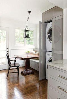 lave-linge et sèche-linge superposés et intégrés dans un placard gris clair doté de portes