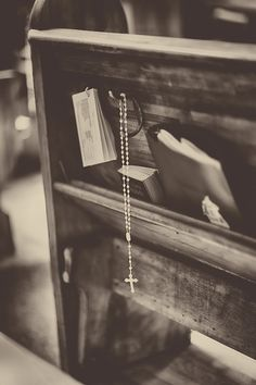Vintage church pew with hymnals and hanging cross prayer beads
