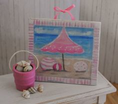 Miniature Painting Of A Beach Scene In Pinks And Blues And A Matching Pink Pail Of Seashells. $12.50, via Etsy.