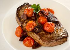 Pan-Seared Sirloin with Tomato-Olive Ragout         4 (4-ounce) sirloin steaks, trimmed      2 tablespoons vegetable oil, divided      3 cups grape tomatoes      ½ teaspoon dried oregano      2 clove garlic, sliced      ⅓ cup pitted Kalamata olives, halved      salt and pepper to taste