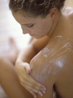 Woman washing her back and shoulders