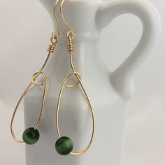 Lazy Hoop Earrings These are simple and elegant and will complement so many outfits. Made with gold wire and a pretty glass cat eye bead. Becky Barnes Designs Jewelry Earrings