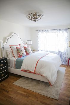 Beautiful bedroom with white arched upholstered bed accented with nailhead trim layered with an orange border duvet and pillow shams alongside orange embroidered sheets and a blue coverlet topped with orange and white floral pillows.