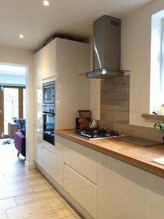 Howdens white gloss intergrated kitchen with solid oak full stave worktops . Wood effect porcelain tiles splashback and neff slide n hide oven Howdens Kitchens, Handleless Kitchen, Home Kitchens, Kitchen Diner Extension, Open Plan Kitchen, Updated Kitchen, Kitchen Living, New Kitchen, Kitchen Decor