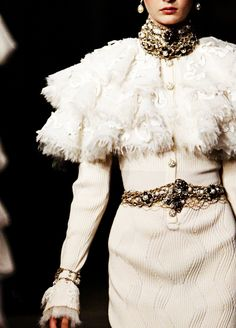CHANEL PRE-FALL 2013 FABRIC: Ribbed textured wool COLOR: Blanc cassé ~ (off white) STYLE FEATURES: Ruffled Capelet neckline with shaggy fringe; very long sleeves with shaggy fringe at wrists; domed buttons Strass ~(Rhinestone)