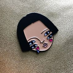 A soft enamel pin badge of one of my original illustrations. The illustration features four eyes, heart cheeks, septum piercing and a tiny glitter teardrop. The badge will be on the backing card pictured and comes with a rubber clutch back.