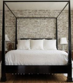 Modern Dark Four Poster Bed juxtaposed with Light Brick Wall