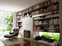 fireplace / bookcase. Window below as opposed to above shelf. Interesting idea.