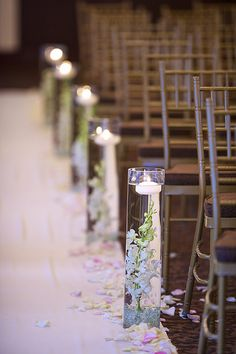 Cylinder vases in varied heights with submerged purple tulips, lavender spray roses and picasso calla lilies will line the aisle.