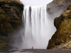 Photo: Hikers are dwarfed by the Skogafoss waterfall, Fimmvorduhals Pass, Iceland.