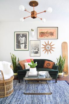 White walls, brown light fixture, green couch, blue rug, glass coffee table, white faux fur throw blankets, basket woven chair, and vintage wall art